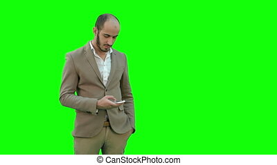 Busy man in suit sending text messages on the phone on a Green Screen, Chroma Key.