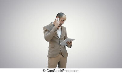 Busy man talking on mobile phone and holding tablet PC on white background.
