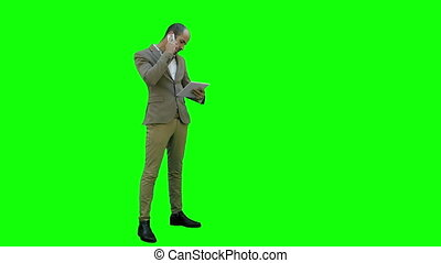 Busy man talking on the phone and holding tablet on a Green Screen, Chroma Key.