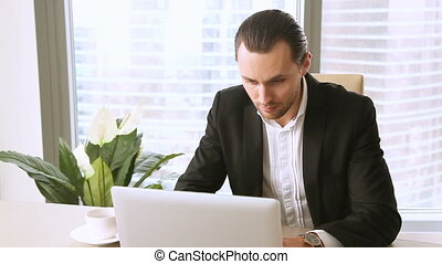 Busy manager meditating at office desk after working on laptop