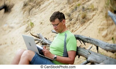 busy mature man working on a laptop computer with business papers picking up a phone to work a call sitting on the beach by the sea on a sunny day and drinking wine from a glass