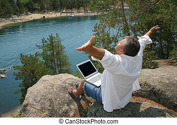 Busy Men on a Holiday - Man working on a laptop on the rocks
