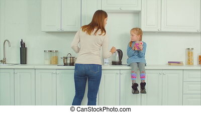 Busy mother doing household chores in the kitchen -...