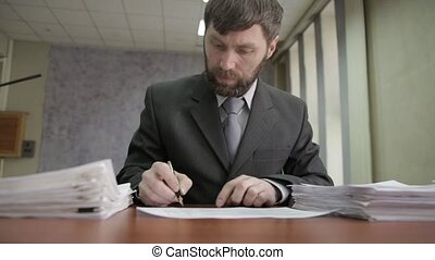 Busy office worker sadly shakes his head, signing and stamping incoming documents