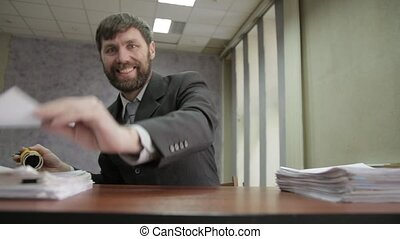 Busy office worker stamping incoming documents. businessman scatter documents around.