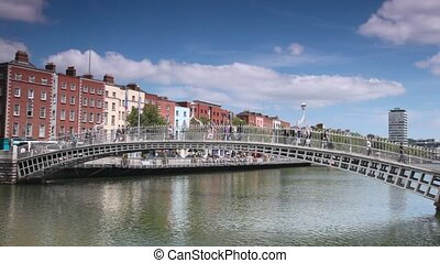 busy people walking on Ha'penny Bridge across River Liffey in Dublin