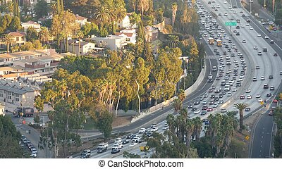 Busy rush hour intercity highway in metropolis, Los Angeles, California USA. Urban traffic jam on road in sunlight. Aerial view of cars on multiple lane driveway. Freeway with automobiles in LA city