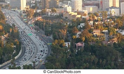 Busy rush hour intercity highway in metropolis, Los Angeles, California USA. Urban traffic jam on road in sunlight. Aerial view of cars on multiple lane driveway. Freeway with automobiles in LA city.