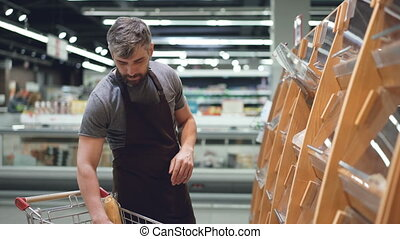 Busy salesman is putting bread on shelves in bakery...
