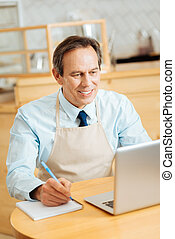 Busy satisfied man sitting and making notices.
