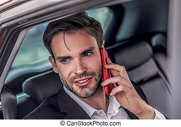 Bearded male sitting at backseat of car, talking on phone