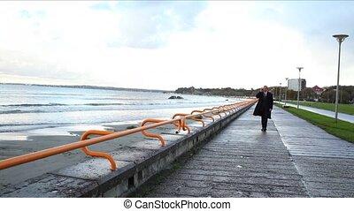 Busy Senior Businessman by Seaside