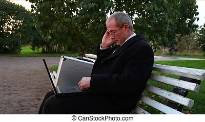 Busy Senior Businessman in Park - Busy elder businessman in...
