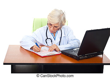 Busy senior woman doctor at desktop
