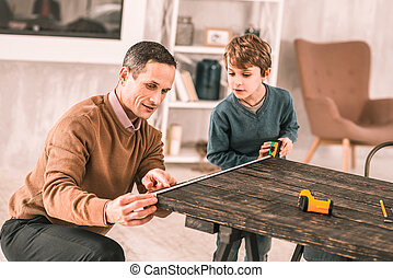 Busy serious man asking his preteen son for help measuring the table.