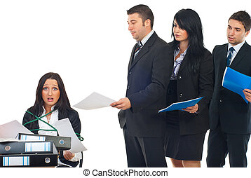 Busy stressed servant public tied in a chair at desktop working hard and other business people standing in a row and waiting their turn to give it to her more folders for work