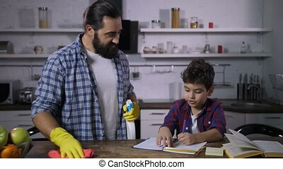 Busy single dad cleaning house while son studying