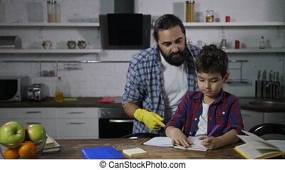 Busy single father helping his son with homework