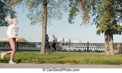 Busy urban people are walking and jogging riding bike in beautiful summer park in river embankment. Summertime and casual city life concept.