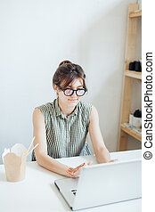 Busy woman designer having lunch in office.