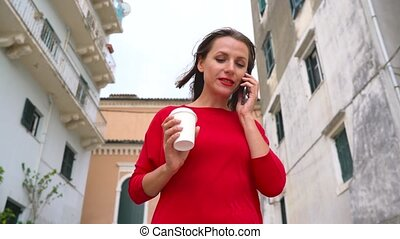 Busy woman talking on the smartphone while runs down the...
