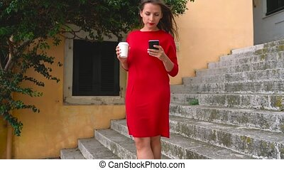Busy woman uses a smartphone on the steps of the street