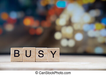 busy word Written In Wooden Cube on wood table with traffic bokeh in background