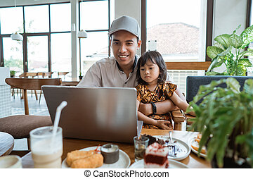 dad with his daughter sitting on his lap