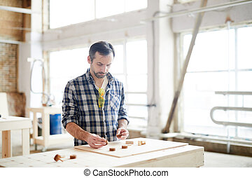 Busy workman comparing small wooden details