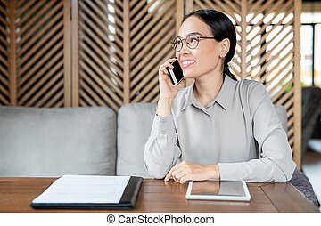 Busy young employee in smart casualwear consulting client on mobile phone
