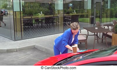 Busy young woman comes to red car and put notebook with cup...