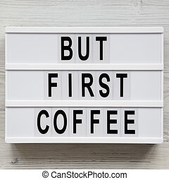 'But first coffee' words on modern board over white wooden surface, top view. Overhead, flat lay, from above.