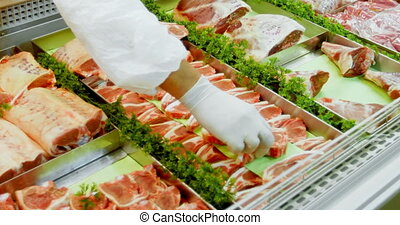 Butcher arranging meat in refrigerator 4k - Butcher...
