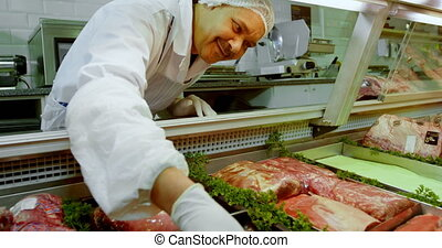 Butcher arranging meat in refrigerator at shop 4k - Smiling...