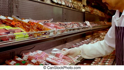 Butcher arranging wrapped meat in rack 4k - Butcher...