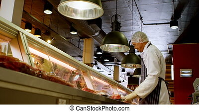 Butcher arranging wrapped meat in refrigerator 4k - Butcher...