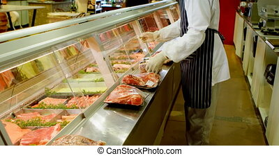 Butcher arranging wrapped meat in refrigerator at shop 4k -...