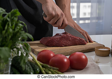 Butcher cutting beef in the kitchen