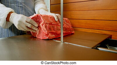Mid section of butcher cutting meat on meat cutting machine in shop 4k