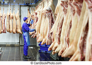 Butcher cutting pork at the meat manufacturing.
