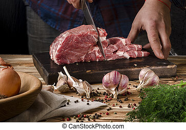 Butcher cutting pork on wooden board on a wooden table on the dark background