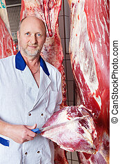 Butcher holding a big lump of raw meat and cutting it with a...