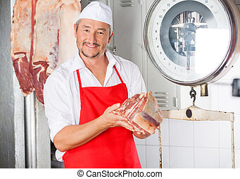 Butcher Holding Meat In Butchery