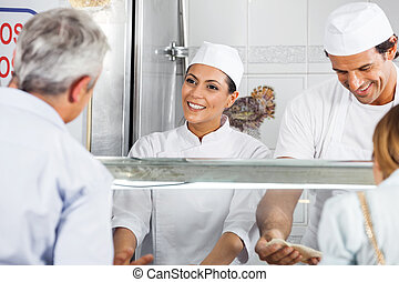 Butcher Looking At Male Customer