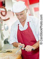 Butcher sharpening a knife