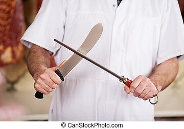 Butcher Sharpening Knife In Shop