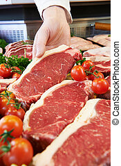 Butcher Showing Customer Sirloin Steak In Refrigerated Display