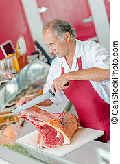 Butcher slicing a big cut of beef