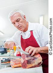 Butcher slicing meat