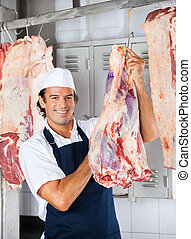 Butcher Smiling While Holding Meat